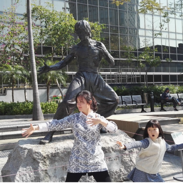 Linyan and Lele play Kung Fu in front of Bruce Lee statue