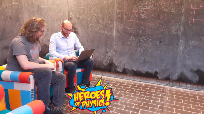 two men look at a laptop in front of a chalkboard wall with the words heroes of physics in comic font nearby