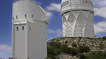 The Bok (left) and Mayall telescopes at Kitt Peak National Observatory near Tucson, Arizona. DESI is currently under installation at the Mayall telescope. (Credit: Michael A. Stecker)