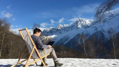 Peter sitting in the snow with a laptop mountains in the background