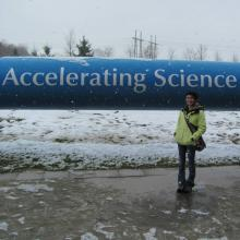 Kelly at CERN in front of a model piece of the LHC