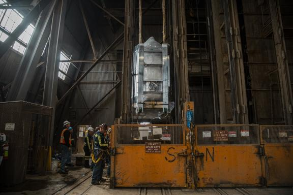 Crews at the Sanford Underground Research Laboratory in Lead, South Dakota, begin to lower the LUX-ZEPLIN central detector. Its nearly mile-long descent down an elevator shaft, and its delivery to a research cavern where it will hunt for dark matter, were successfully carried out last week. (Credit: Nick Hubbard/Sanford Underground Research Facility)