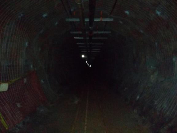 Dark tunnel with a few lights at its end