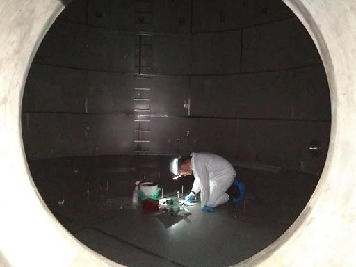 engineer painting the bottom of a water tank
