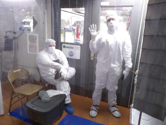 two researchers in full-body white coverings, white masks, shoe covers and hoods.