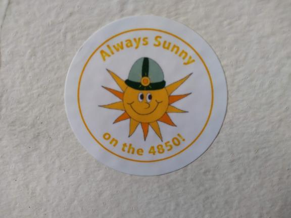 "A sticker of a cartoon Sun wearing a miner helmet with a caption ""Always Sunny on the 4850!"""