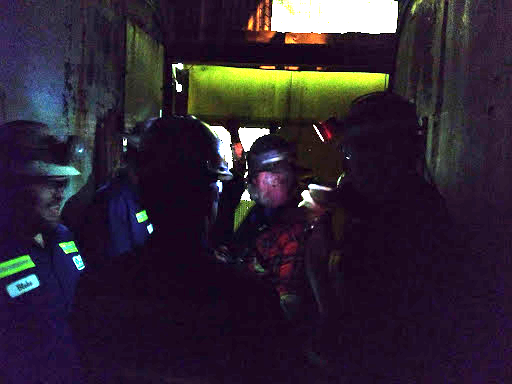 A very dark photo of people in a mining elevator